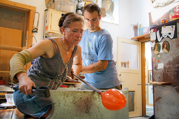 Katrina Hude and her assistant shaping a canework vase. (Photo by David Welton)