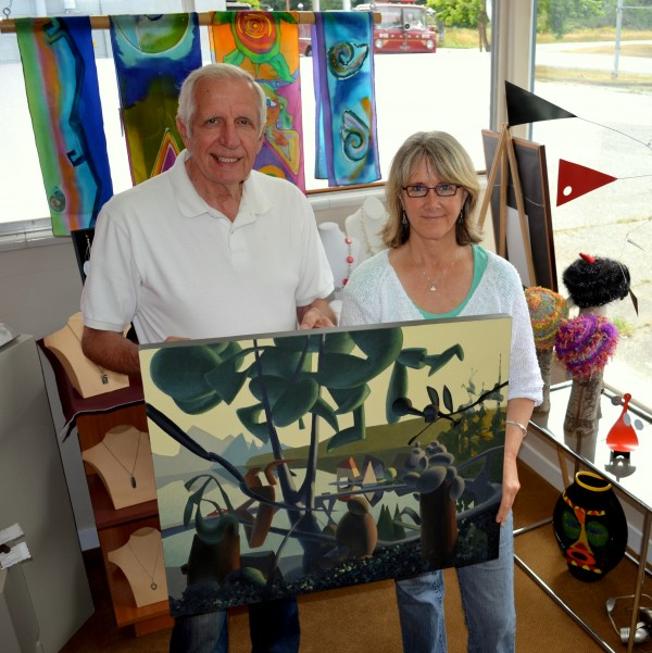 Inspired Arts gallery owners Ron Roesler and Sue Averett hold up a painting by Mark Skullerud. (Erick Westphal photo)