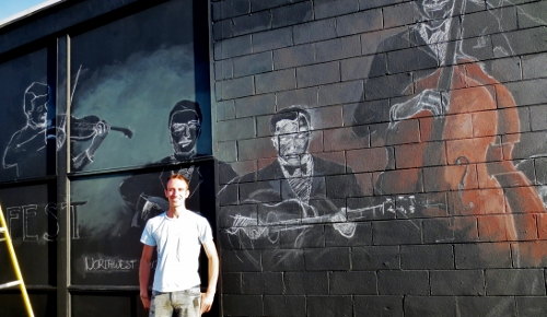 Matt Statz stands in front of his DjangoFest mural at Whidbey Island Center for the Arts in Langley. (Betty Freeman photos)