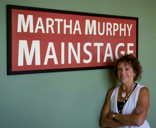 WCT founding artistic director Martha Murphy stands under the sign that reveals her namesake stage dedicated to her at the Porter Building in Langley. (Levi Burkle photo)