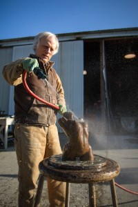 Sculptor Lloyd Whannell applies patina to a bronze, then washes off the chemicals. (Photo by David Welton).