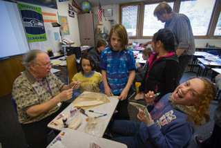 Good helps Victoria Alumbaugh, Magnus Nyberg, Linzey Allen, and Erin Baublitz assemble their gliders. Behind them, their teacher, John LaVassar, helps another classmate