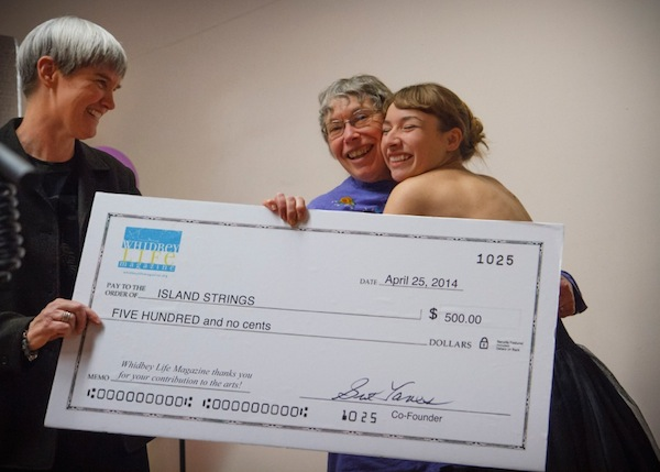 Publisher Sue Taves and musical guest present the first WLM Arts Grant to Linda Good and Island Strings (photo by David Welton).