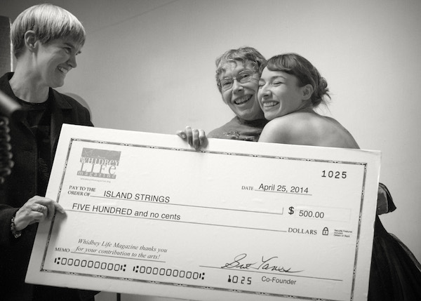 Linda Good receives the first WLM Arts Grant from publisher Sue Taves and an appreciative hug from former student Gloria Ferry-Brennan. (photo by David Welton)