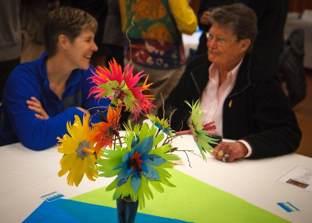 Peggy Moe's paper flower centerpieces help create unique and fun mood as local photographers and art supporters Ruth Cox (left) and Sharon Shoemaker enjoy the evening.