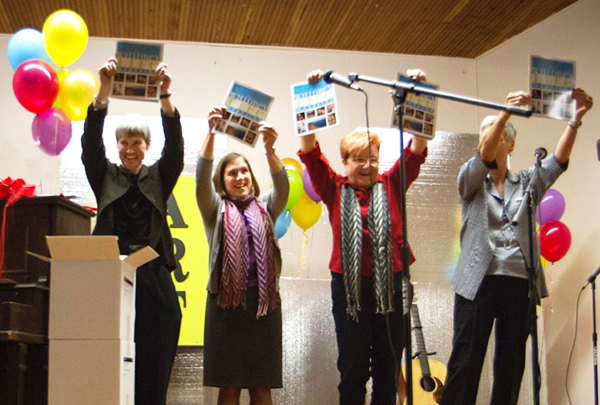 The magazine, at last, held aloft by Sue Taves, publisher; Helen Price Johnson, Island County Commissioner, District 1; Claire Moore, co-editor and Marsha Morgan, MC for the event. (photo by David Welton)