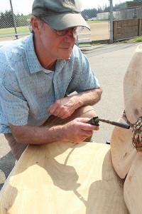 Pat McVayuses a torch to burnand darkenthe centers of dogwood blossoms. (photobyMartha McCartney)