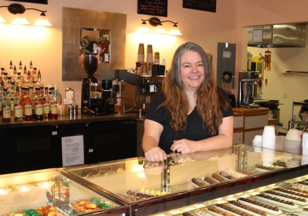 Mona Newbauer stands ready to welcome her customers to her new, much larger shop.