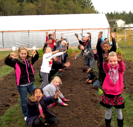 Kids are not afraid to get their hands dirty in the garden adjacent to the hoophouse. Photo by Cary Peterson