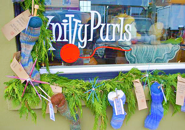 Knitty Purls displays wool stockings with knitting needles for stars by Mary McLeod.