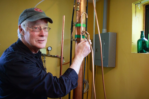 Owner Steve Heising adjust the valves of the continuous still  (photo by Steve Kilisky)
