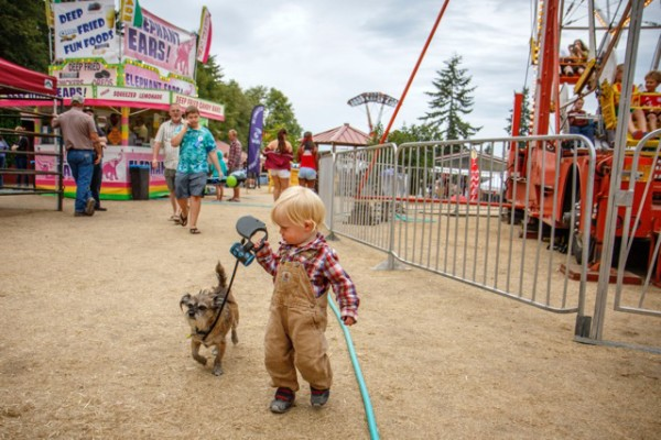 Genghis Carrol walks his dog Baxter between the Ferris Wheel and the elephant ear concession.    (photo by David Welton)