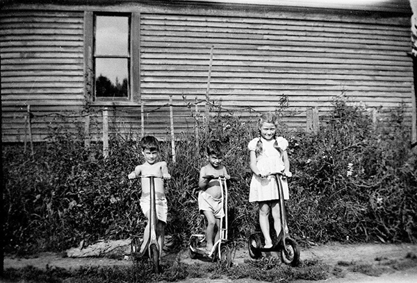Mary Sue and her brothers, with their scooters beside the house, a year before the fire. (photo courtesy of the family)