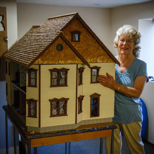 Mary Sue points, on her dollhouse replica, to where the fire began.