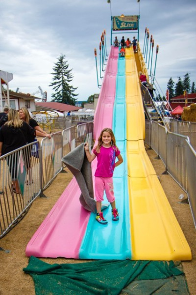 A young girl proudly negotiates the perils of the big slide.    (photo by David Welton)