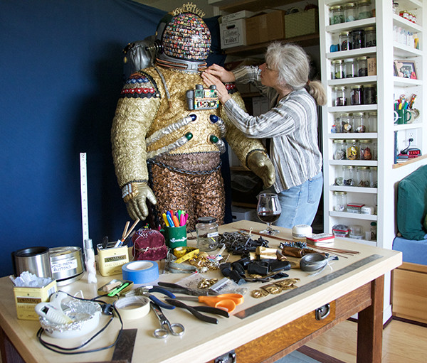 "Pfeifer working on ""Kit"" behind some of the objects she included (photo by Marsha Morgan)"