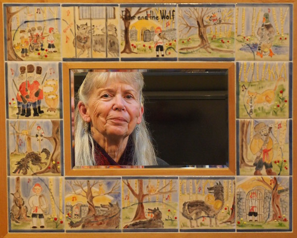 Roxallane Medley looks into the mirror made up of her hand-painted tiles with scenes from Peter and the Wolf (photo by David Medley)
