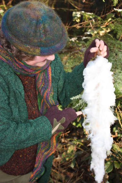 "Susan Zwinger pauses in her walk in the woods to examine an ""ice feather."" (photo by Susan Scott)"