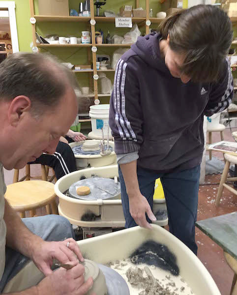 Tom Brown at the wheel , coached by instructor Sharon Warwick of Wellspring Pottery (photo by Vicky Brown)
