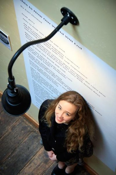"South Whidbey High School junior Kari Hustad stands in front of her poem ""This Is the Way the World Will End."" (Photo by David Welton)"