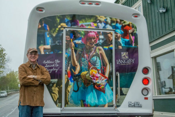 David Welton poses next to one of his photos on the SeaTac Airport Shuttle. (Photo by Marsha Morgan)