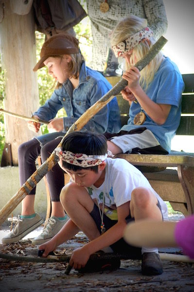 Students learning to carve staffs as taught by Angeles Peña (photo by Norma Fickel)