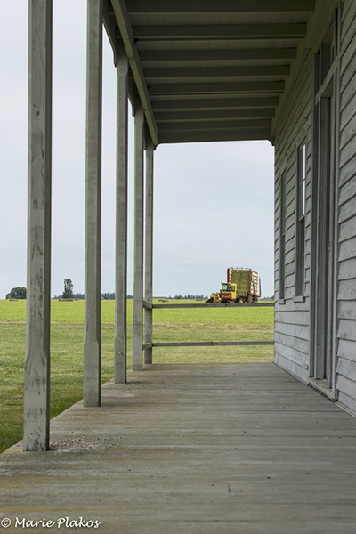 The porch of an old house is a marked contrast to the modern harvester. (photo by Marie Plakos)