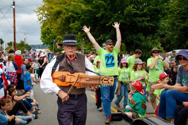 Dan Anderson, in traditional Swedish garb marched with Island Strings as he played his Nickel Harpa.