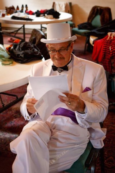 Tim Callison, in his white tuxedo, reviews off-color vaudeville jokes