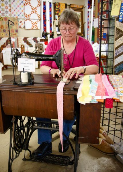 "Anita Smith demonstrates a foot powered antique sewing machine. She vows to ""save the treadle""."