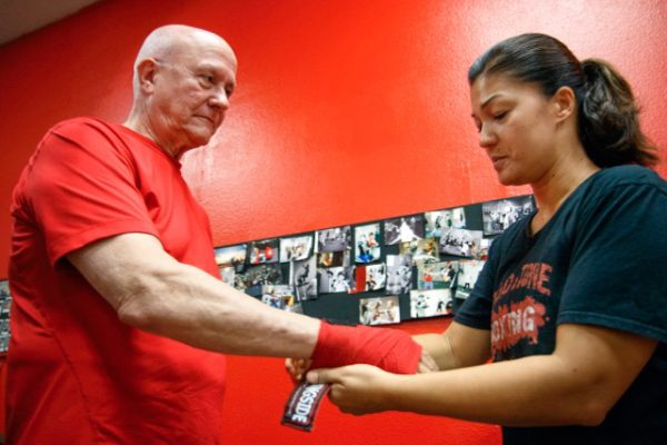 Before putting on gloves, Coach Donna Parsell applies hand-wraps to protect the boxer's knuckles and wrists.