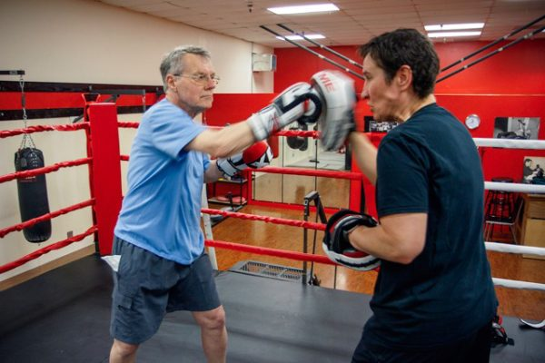 """Using """"punch mitts"""" as a target, boxers can put what they're learning to practical use."""