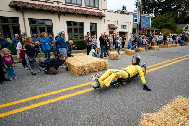 A street luge with handbrakes crosses the finish line first and exits the course.