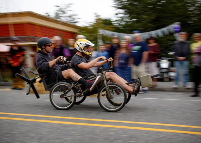 A four-wheeled tandem racer, with a concrete block counterweight extending over the front-end, speeds by the crowd in front of Music for the Eyes.
