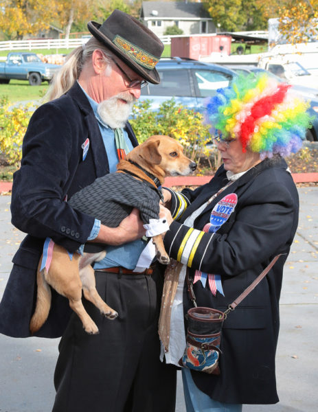 Man in hat and woman in rainbow wig with dog in suit
