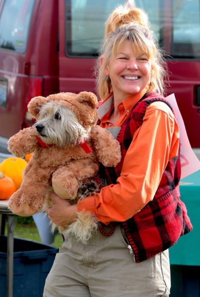 Woman holds dog in teddy bear costume.