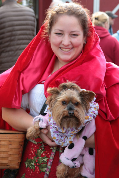 A woman in a Red Ridinghood costume with a costumed dog.