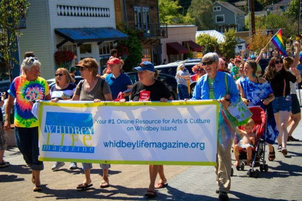 Four women holding a Whidbey Life Magazine banner marching in a parade. (photo by David Welton)