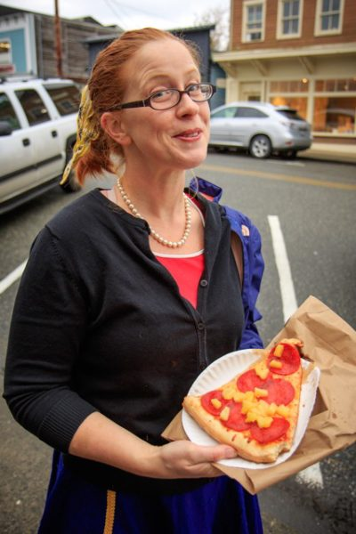 Woman with slice of pizza.