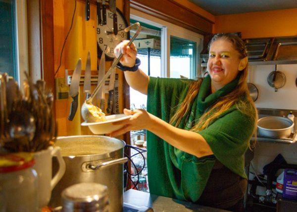 Woman ladling soup into bowl