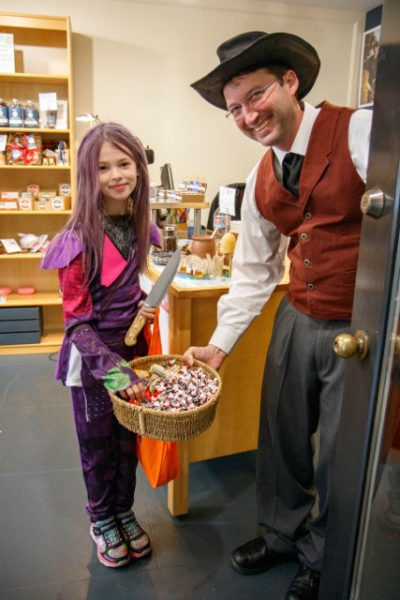 Costumed man holding basket of candy for child to choose from.