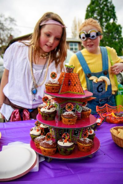 Costumed children looking at decorated cupcakes