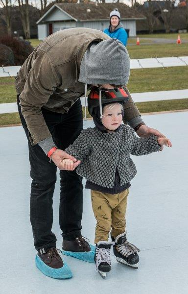 Adult holding hands of young child on skates