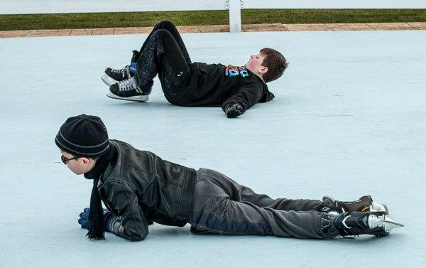 Two boys lying on ice
