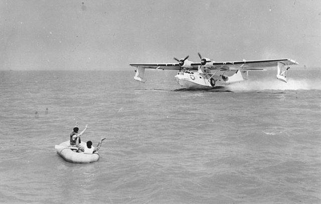 People in life boat waving at landing PBY